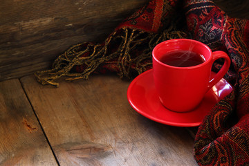 Cup of tea with fashion scarf on wooden table