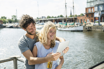 Germany, Luebeck, happy couple at the harbor with digital tablet