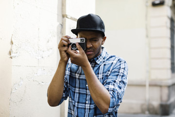 Young man with baseball cap and camera taking photos on the street