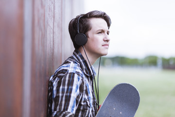 Teenage boy with skateboard leaning on corten wall hearing music
