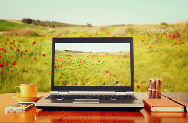 laptop over wooden table outdoors and blurred field of flowers