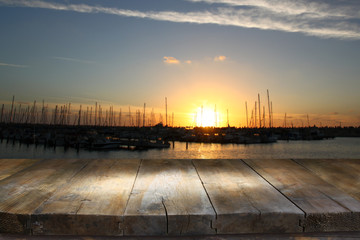image of wooden table in front of abstract blurred background of marina yacht in pier at sunset