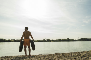 Young man in swimming shorts with inner tubes by the riverside