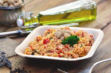 Couscous Salat - Taboulé, in Palmblatt-Teller / rustikal mit Besteck auf Holz