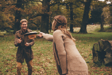 Young couple playing with a hat in an autumnal park
