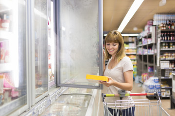 Cute woman chooses frozen products in supermarket