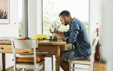 Young man at home using sewing machine