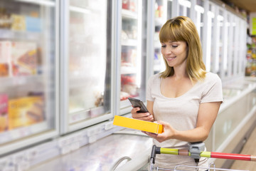 Cheerful woman using a mobile phone in supermarket. QR Code. Texting