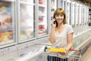 Cheerful young woman on smart-phone in supermarket. looking camera