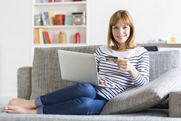 Thirty year old woman shopping using laptop and credit card at home