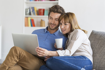 Happy successful young couple with laptop on sofa in modern apartment