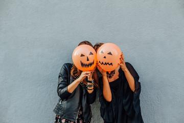 Girls hiding behind Halloween balloons
