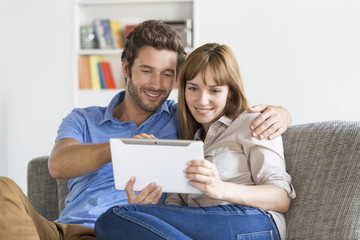 Young couple consulted their next trip on app tablet pc at home