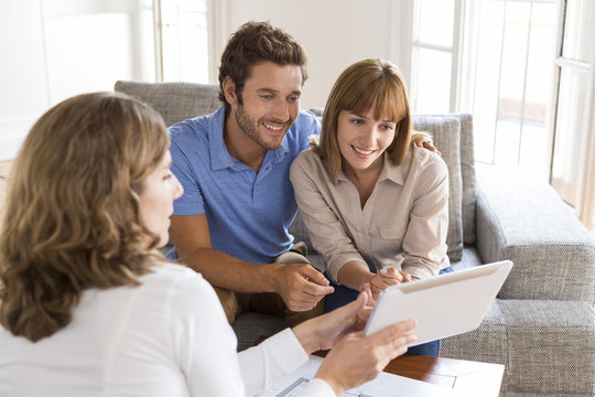 Real-estate agent presenting to a couple a project property on tablet PC