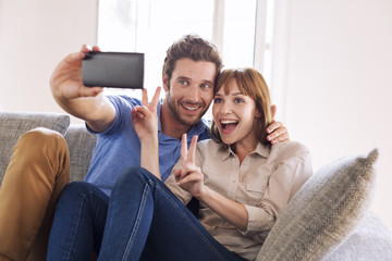 Happy fun couple taking a selfie with a mobile phone