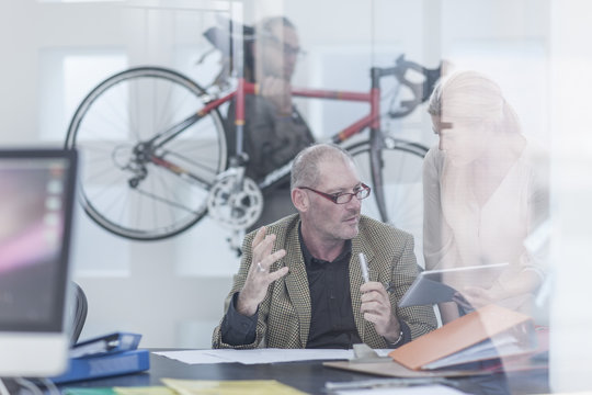 Businesspeople discussing in office, on carrying bike in background