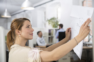 Smiling woman in office looking at plan