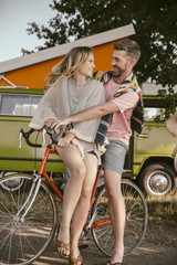 Happy couple on a bicycle in front of van in the nature