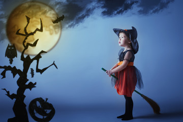 Halloween. Witch child flying on broomstick at sunset night sky.