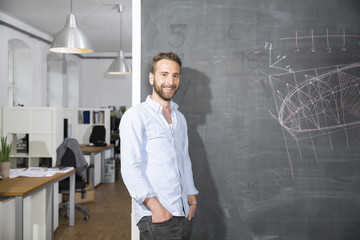 Smiling young man standing at blackboard in office