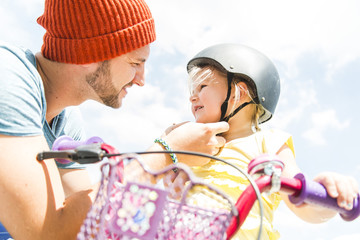 Father closing daughter's helmet on bike