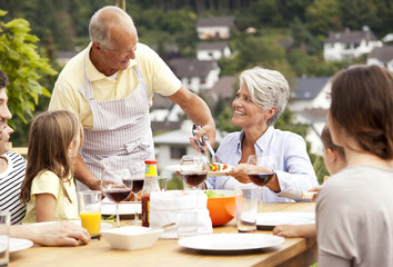 Grandfather serving food from barbecue grill for family at garden table