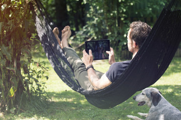 Relaxed man lying in hammock with digital tablet and dog beside him