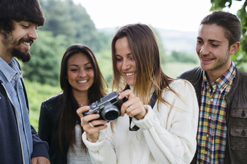 Group of four friends with a camera