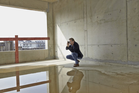 Man taking picture on construction site in unfinished building