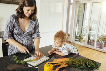 Pregnant woman cutting vegetables with her son in the kitchen