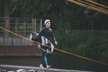 Young man carrying his wakeboard