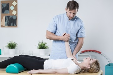 Handsome physiotherapist working with patient