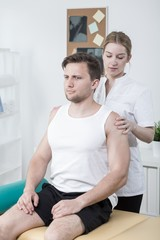 Therapist examining athletic man