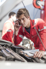 Car mechanic with mobile phone in repair garage