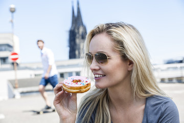 Germany, Cologne, portrait of young woman eating bagel