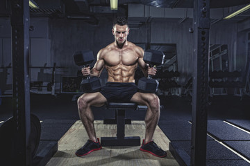 Physical athlete doing dumbbell bench presses