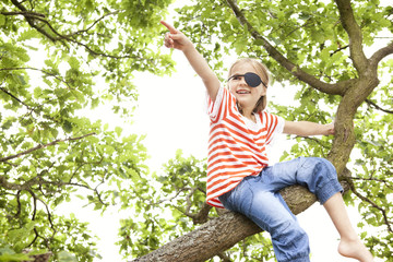 Girl dressed up as pirate sitting on a tree pointing finger