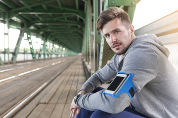 Young athletic man with wearable computer sitting on bridge
