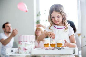 Girl garnishing cup cakes, familiy celebrating in background