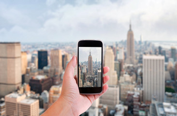 Hand with smartphone taken pictures of new york city skyline