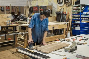 Carpenter using grinding machine in workshop