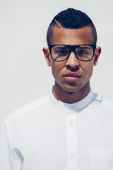 Portrait of young man with shaved hair and glasses wearing white shirt in front of white background