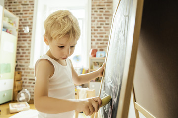 Little boy drawing on chalk board in children's room