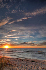 Sunset from a tropical desert beach with pastel colors, clouds and reflection
