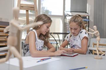 Two girls using digital tablet in an art class