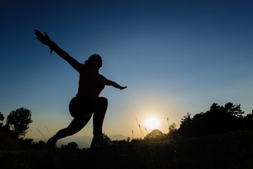 silhouette of young women who exercise at sunset