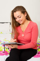 young woman writing sitting on her bed