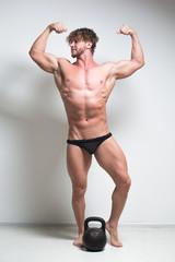 bodybuilder against a white wall.  kettlebell