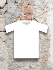 T-shirt hung with clothespin on rough wall background