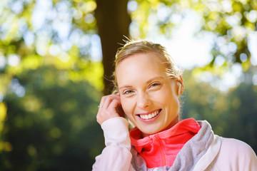 lachende junge frau hört musik beim joggen